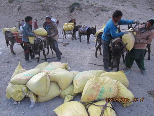 Cementsäckar lastas för transport till skolhemmet